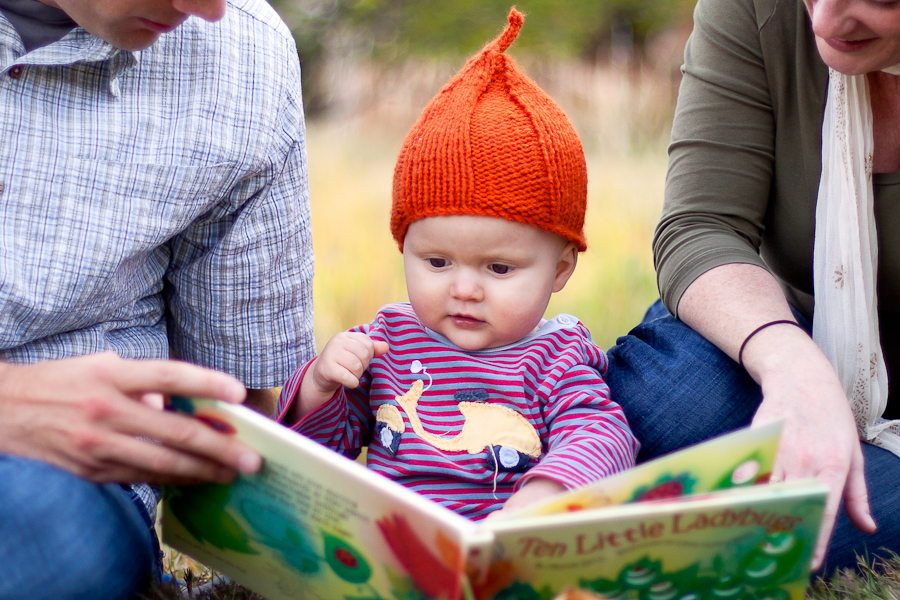 toddler in hat reads with parents